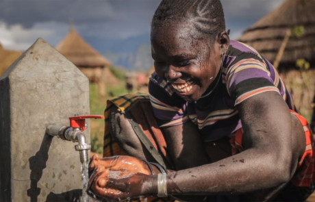 text to give video report showing Ugandan boy benefitting from donor funded clean water installation project 460x295 Video Marketing and Storytelling at Your Level of Budget and Expertise %page