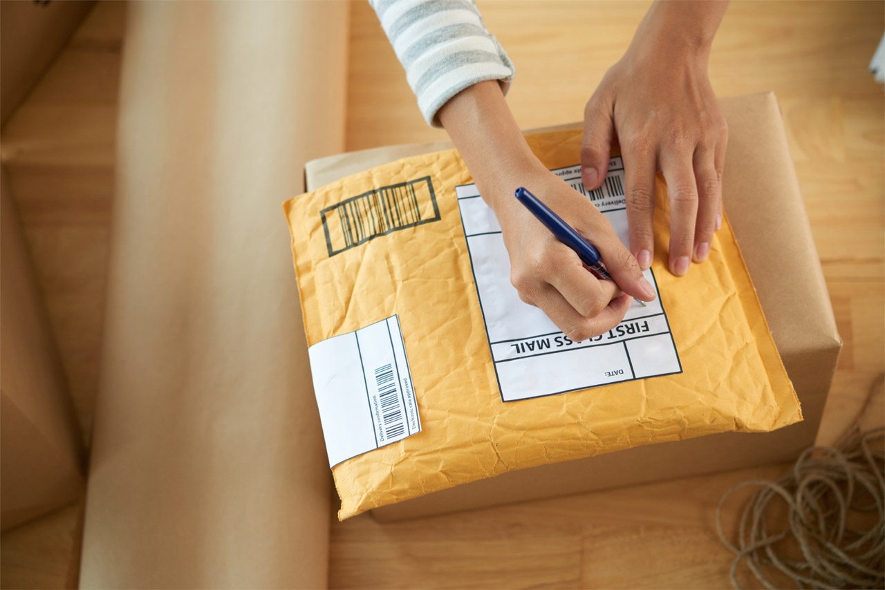 woman addressing small package for mailing from home office