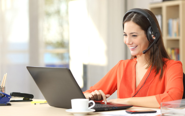 woman wearing orange blouse working home office laptop conference call