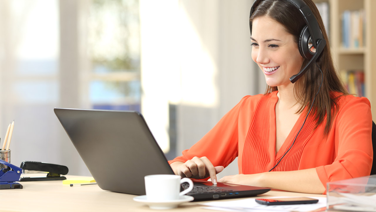 woman wearing orange blouse working home office laptop conference call coffee cup Tips on Working from Home %page
